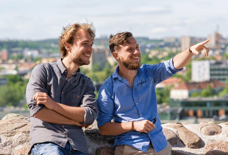Jonge mens die iets tonen die aan zijn vriend Litouwen interesseren stock fotografie