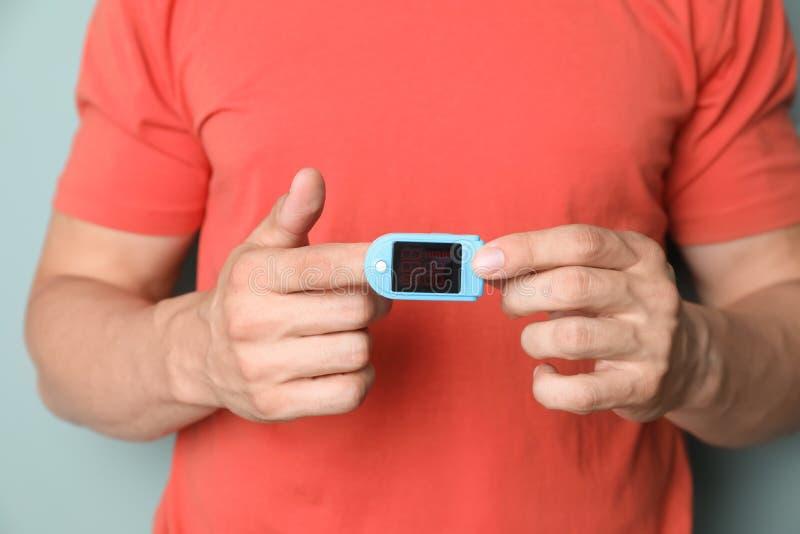 Jonge mens die impuls met bloeddrukmonitor controleren op vinger stock foto