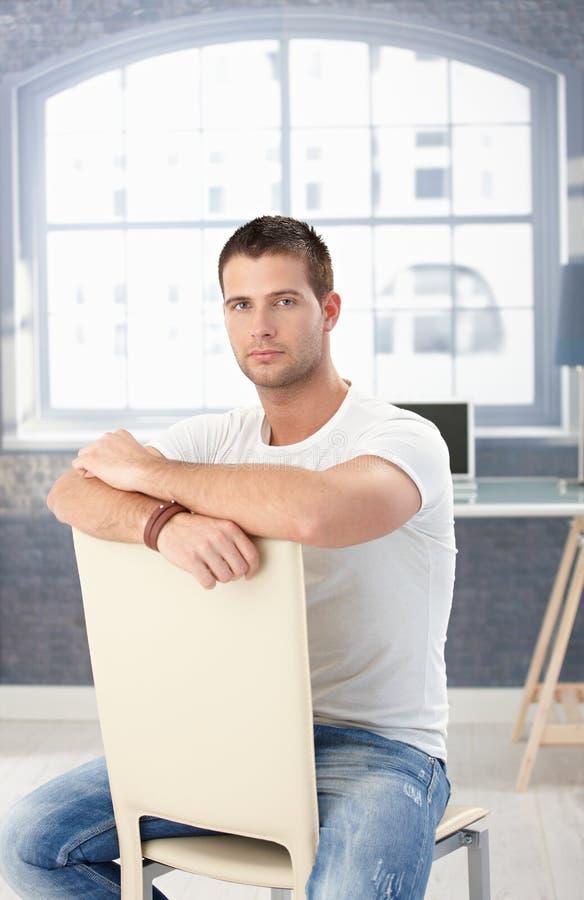Jonge mens die in jeans omgekeerd op stoel zit stock foto's