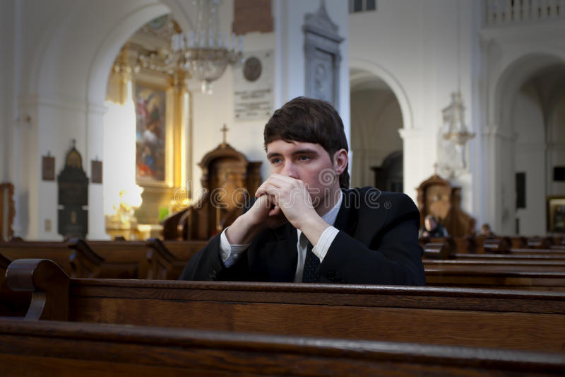 Jonge mens die in kerk bidt stock fotografie