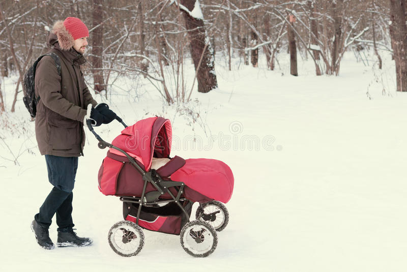 Jonge mens die kinderwagen met baby in de winterpark wandelen royalty-vrije stock fotografie