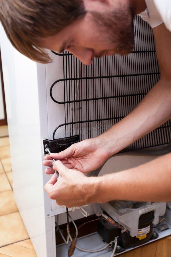 Jonge mens die koelkast herstellen stock afbeeldingen