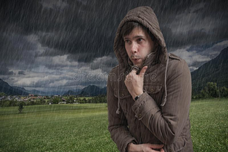 Jonge mens die koud tijdens onweersbui voelen stock fotografie