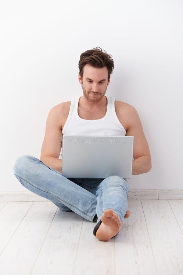 Jonge mens die laptop bij vloer het glimlachen met behulp van royalty-vrije stock afbeelding