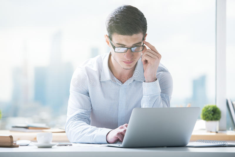 Jonge mens die laptop computer met behulp van stock foto