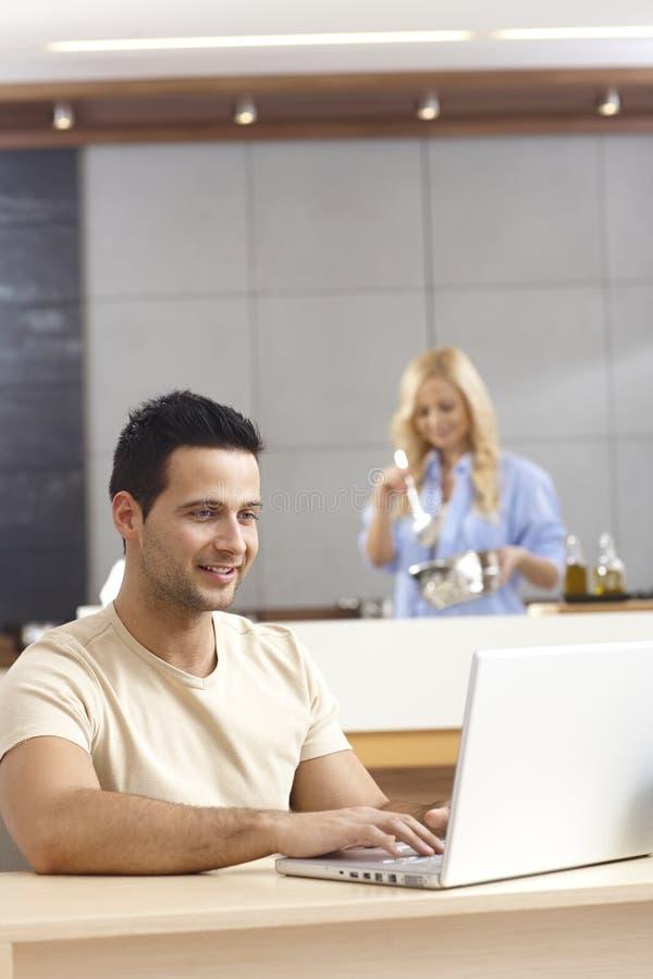 Jonge mens die laptop computer thuis met behulp van royalty-vrije stock foto