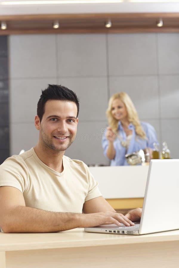 Jonge mens die laptop computer thuis met behulp van stock fotografie