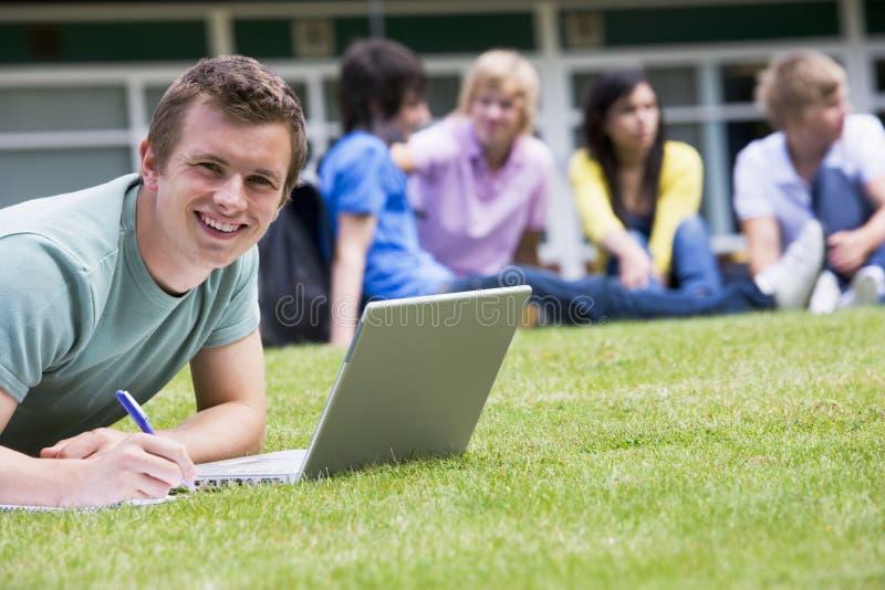 Jonge mens die laptop op campusgazon met behulp van royalty-vrije stock foto