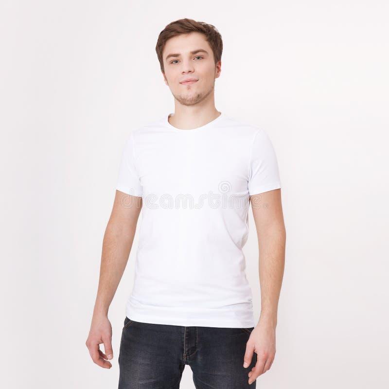 Jonge mens die lege witte die t-shirt dragen op witte achtergrond wordt geïsoleerd De ruimte van het exemplaar Plaats voor reclam stock foto's