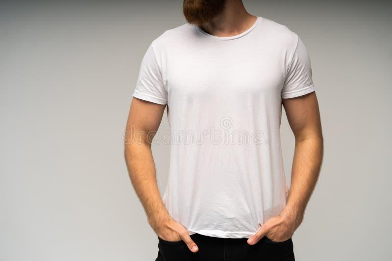 Jonge mens die lege witte die t-shirt dragen op witte achtergrond wordt geïsoleerd De ruimte van het exemplaar Plaats voor reclam stock fotografie