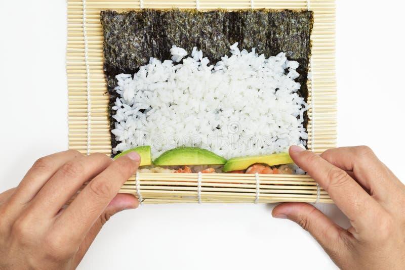 Jonge mens die makizushi voorbereiden stock foto