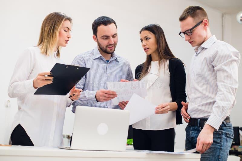 Jonge mens die marktonderzoek bespreken met collega's in een vergadering Team van beroeps die gesprek hebben bij royalty-vrije stock afbeelding