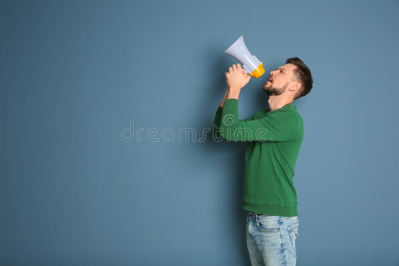 Jonge mens die in megafoon schreeuwen stock foto
