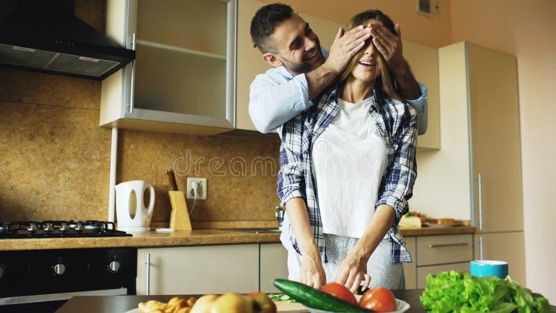 Jonge mens die meisjesogen behandelen met handen en haar thuis verrassen in de keuken royalty-vrije stock foto