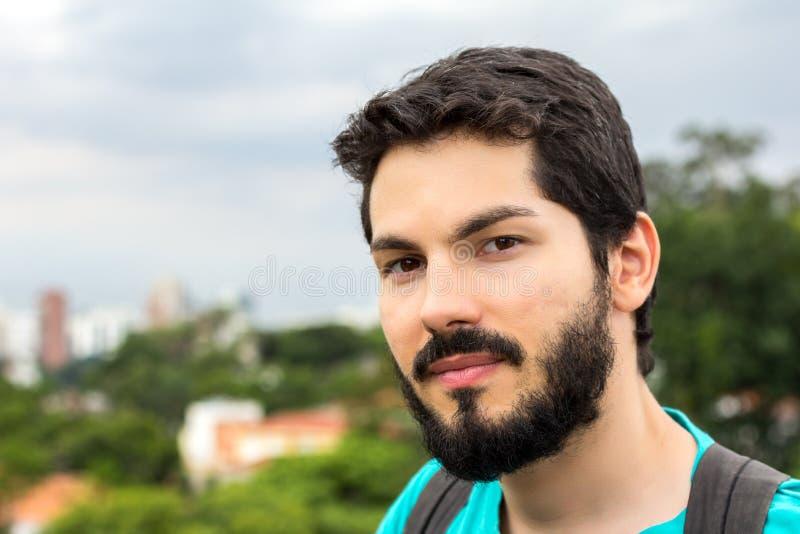 Jonge mens die met baard camera bekijken stock afbeeldingen