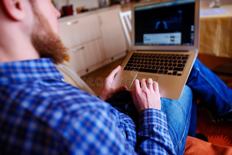 Jonge mens die met computer aan het strand werken Knappe mens die met laptop die aan de laag werken bij het strand leggen stock fotografie