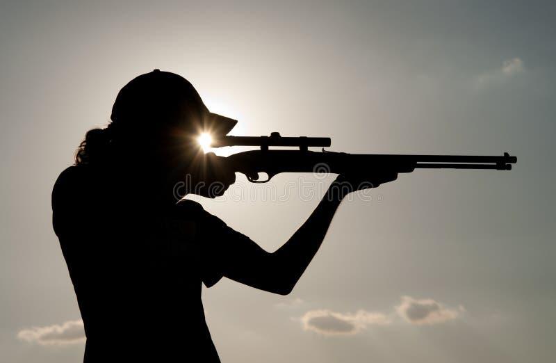 Jonge mens die met een geweer ontspruit stock afbeeldingen