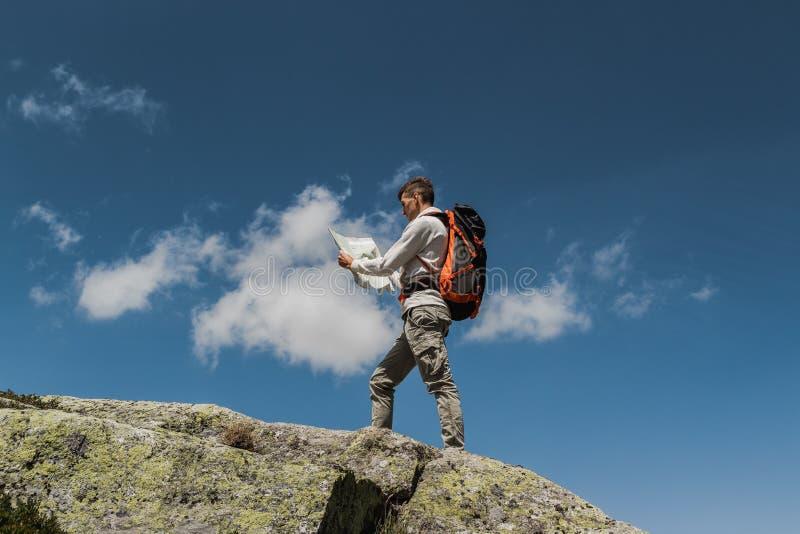 Jonge mens die met grote rugzak de bovenkant van de berg tijdens een zonnige dag lopen te bereiken Het lezen van een kaart stock afbeelding