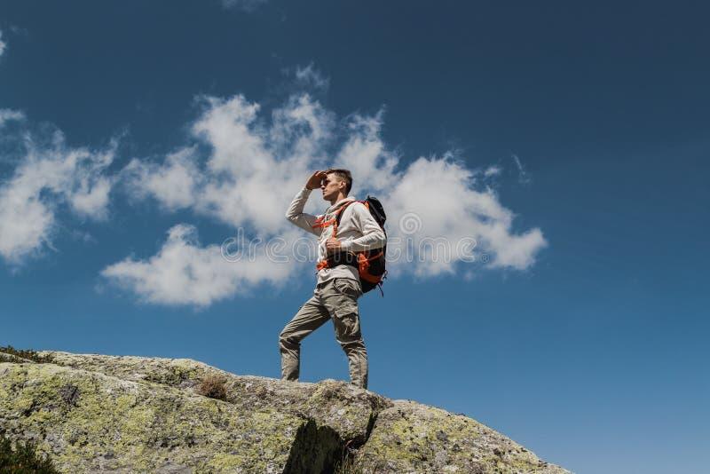 Jonge mens die met grote rugzak de bovenkant van de berg tijdens een zonnige dag lopen te bereiken het overwegen van het panorama stock fotografie