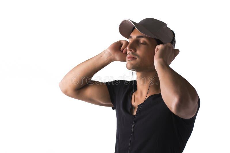 Jonge mens die met hoofdtelefoon aan muziek luisteren royalty-vrije stock afbeeldingen