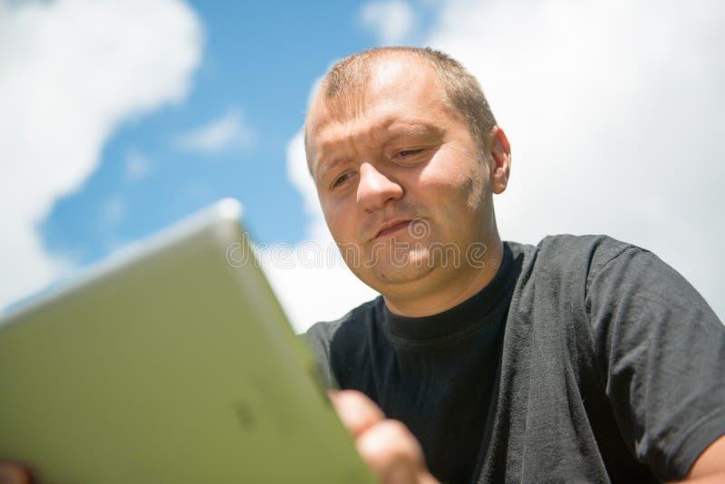 Jonge mens die met ipad werkt stock afbeelding