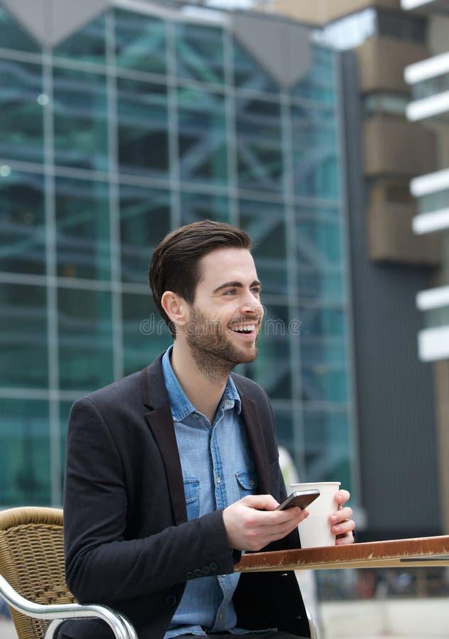 Jonge mens die met mobiele telefoon glimlachen royalty-vrije stock foto's