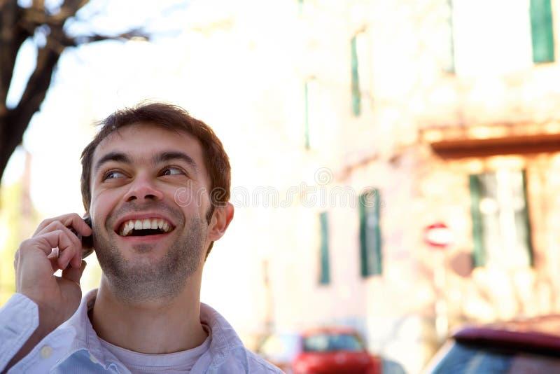 Jonge mens die met mobiele telefoon in openlucht roepen royalty-vrije stock afbeeldingen