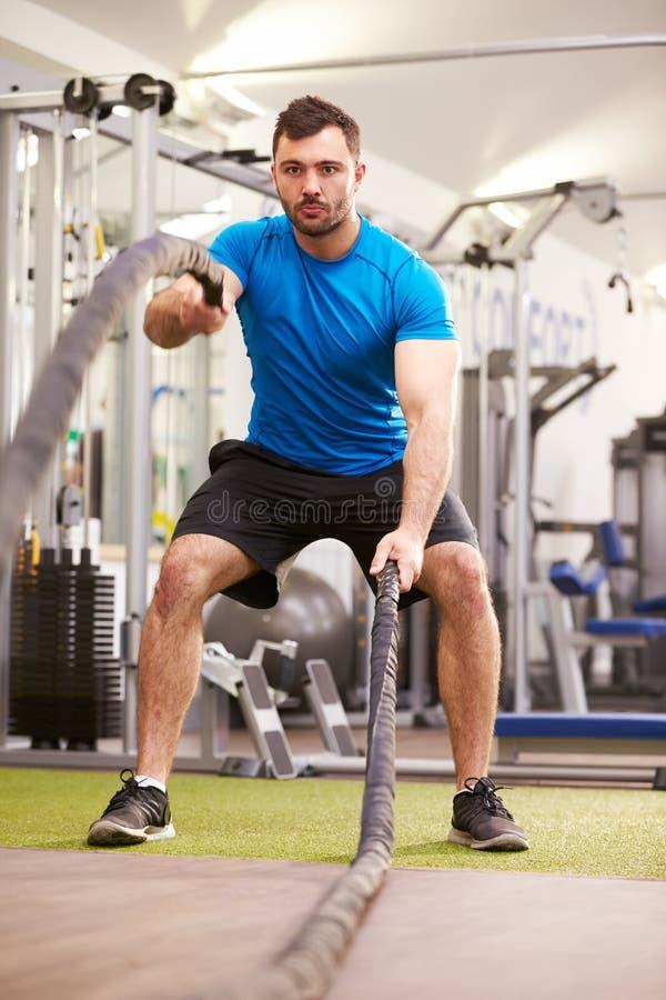 Jonge mens die met slagkabels bij een verticale gymnastiek uitwerken, stock foto's