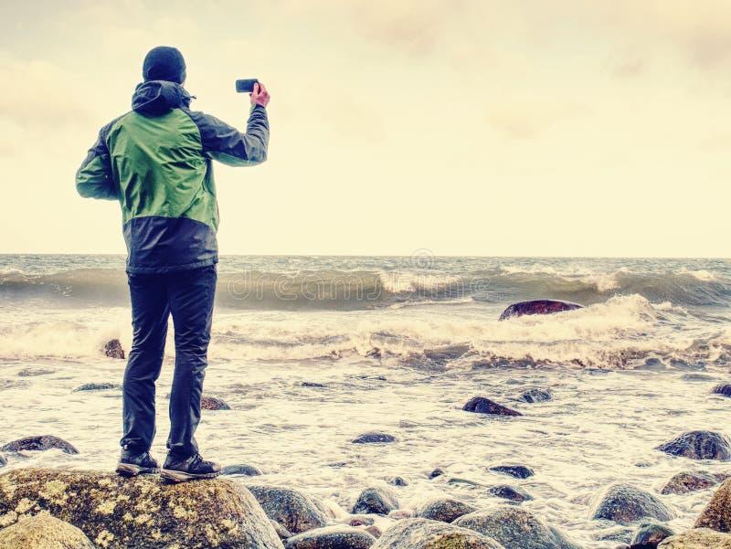 Jonge mens die met toeristisch kostuum op verbazend zeegezicht kijken stock afbeelding