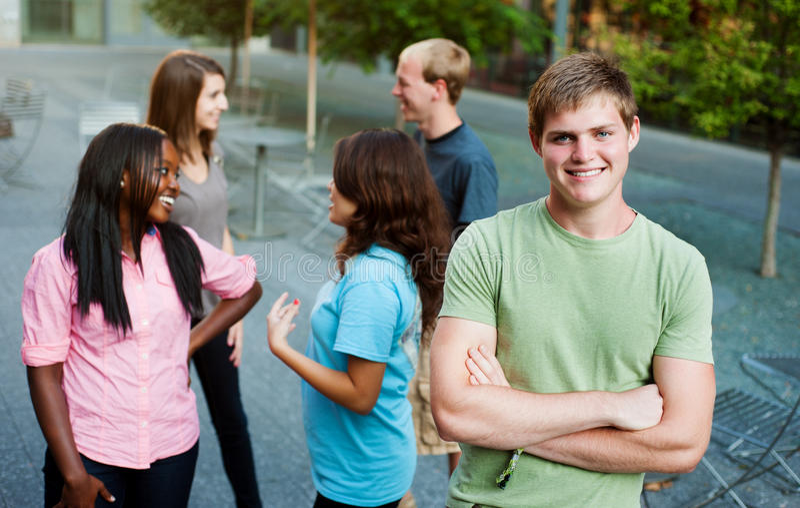 Jonge mens die met vrienden glimlacht royalty-vrije stock fotografie