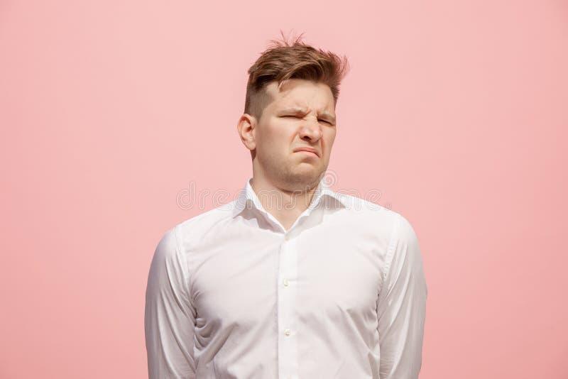 Jonge mens die met weerzinwekkende uitdrukking iets afwijzen, geïsoleerd op het roze stock afbeelding