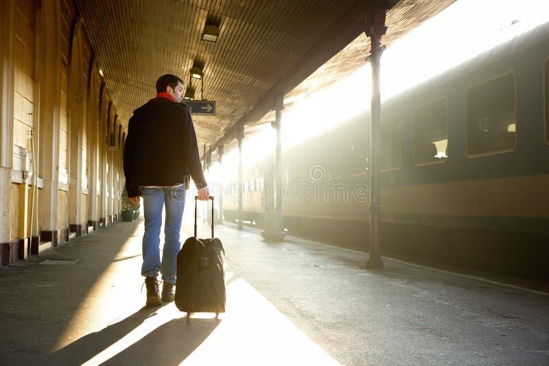 Jonge mens die met zak bij station lopen stock afbeeldingen