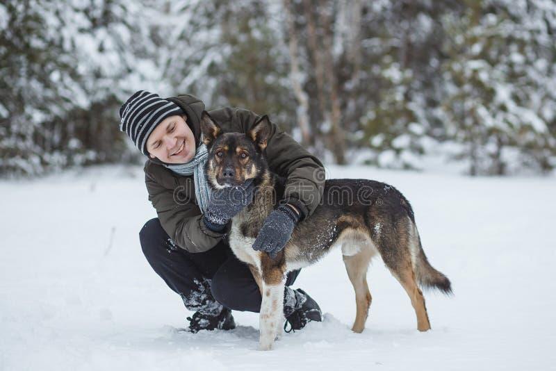 Jonge mens die met zijn herdershond in het bos van de de winternaaldboom lopen stock afbeeldingen