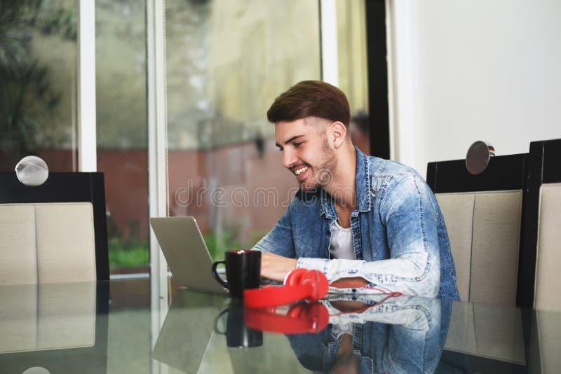 Jonge mens die met zijn tablet, hoofdtelefoons en koffie bestuderen stock afbeeldingen