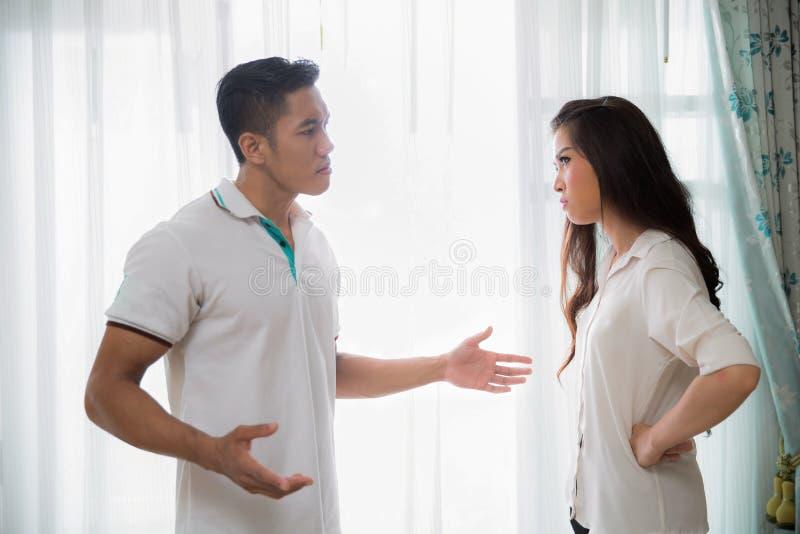 Jonge mens die met zijn vrouw ruzie maken thuis terwijl het gillen en s stock foto's