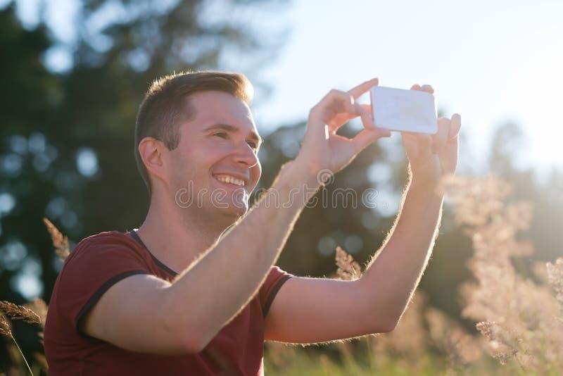 Jonge mens die mobiele telefoon in handen houden bij zonsondergang die een foto van aard op telefoon maken royalty-vrije stock afbeeldingen