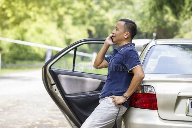 Jonge mens die mobiele telefoon met behulp van bij het park royalty-vrije stock afbeeldingen