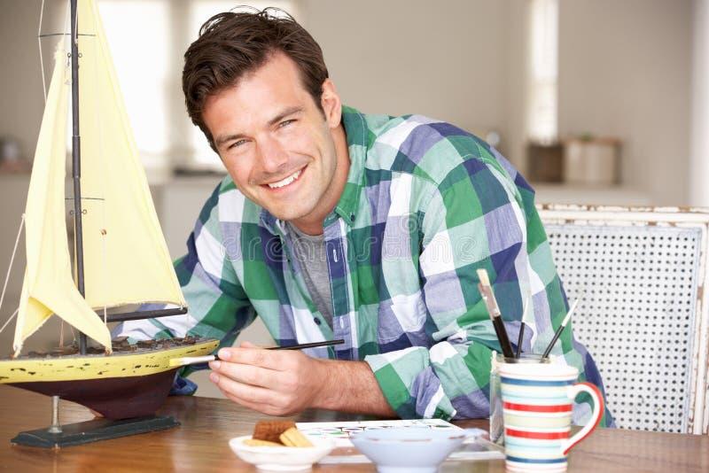 Jonge mens die modelschip schildert stock foto