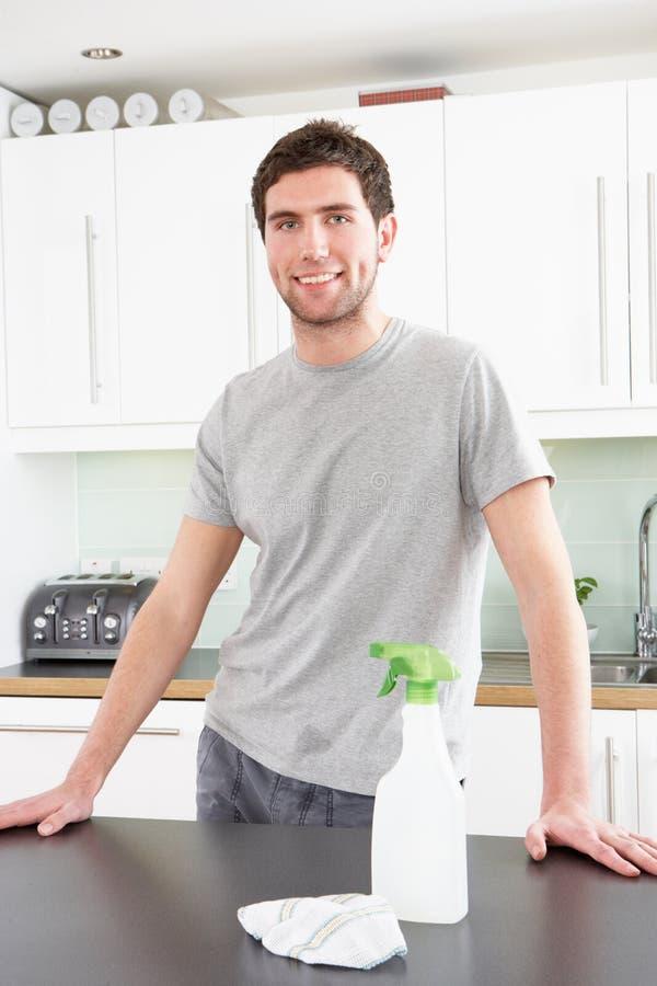 Jonge Mens die Moderne Keuken schoonmaakt royalty-vrije stock afbeelding