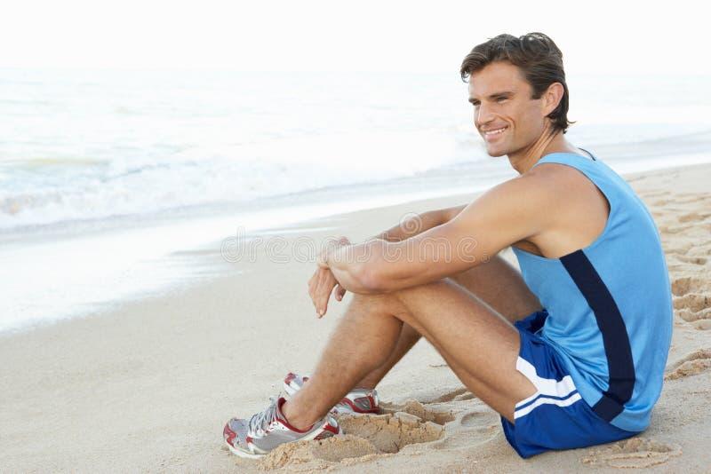 Jonge Mens die na Oefening op Strand rust stock afbeeldingen