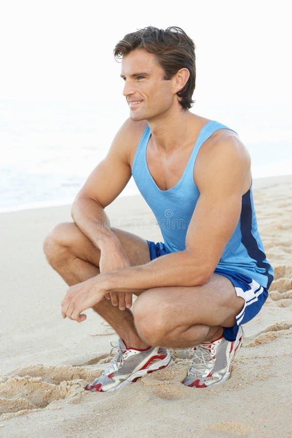 Jonge Mens die na Oefening op Strand rust royalty-vrije stock foto's