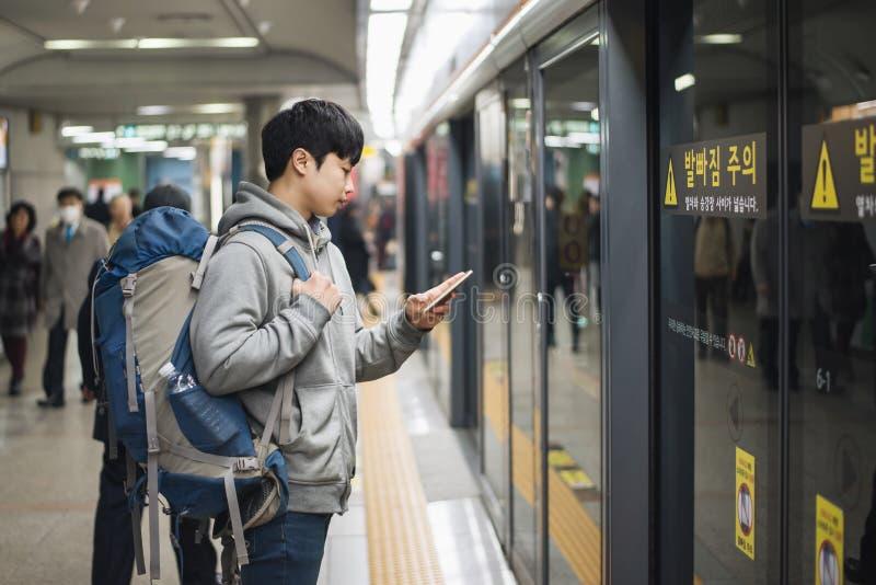 Jonge mens die naar Korea, mannetje reizen die op metro wachten stock afbeelding