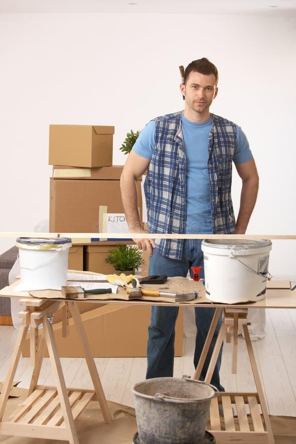 Jonge mens die nieuw huis voorbereidingen treft te schilderen stock foto's