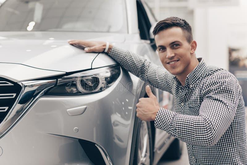 Jonge mens die nieuwe auto kopen bij het handel drijven stock afbeelding