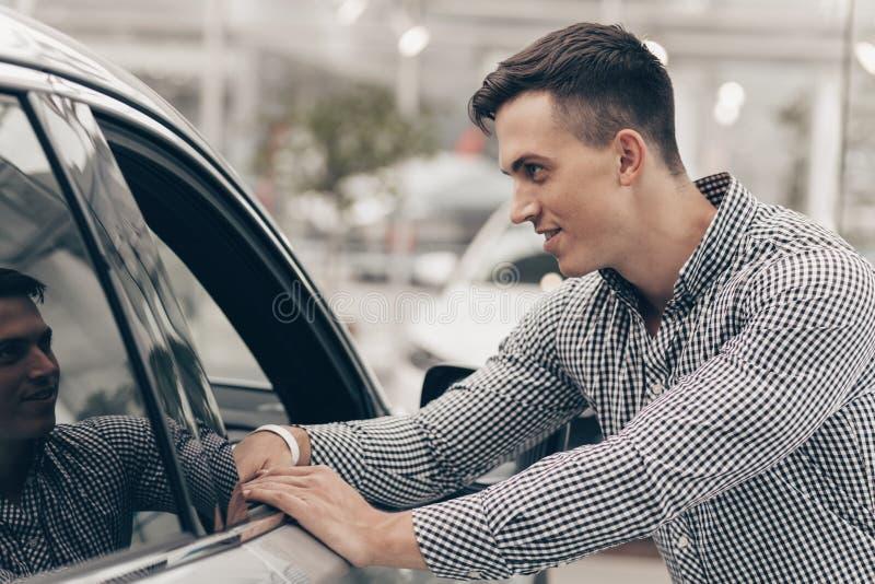 Jonge mens die nieuwe auto kopen bij het handel drijven stock afbeeldingen