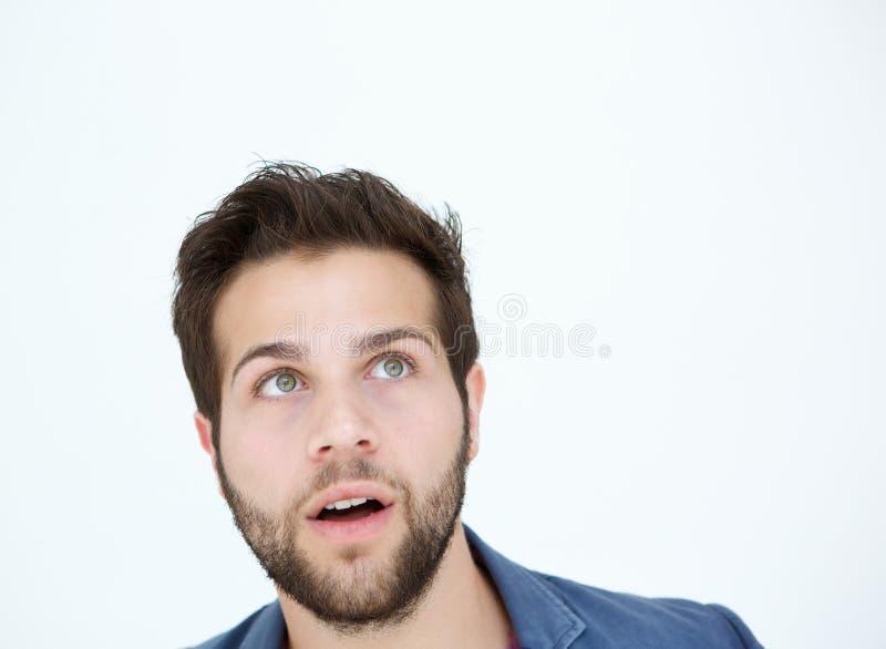 Jonge mens die omhoog met verraste uitdrukking kijken royalty-vrije stock foto's