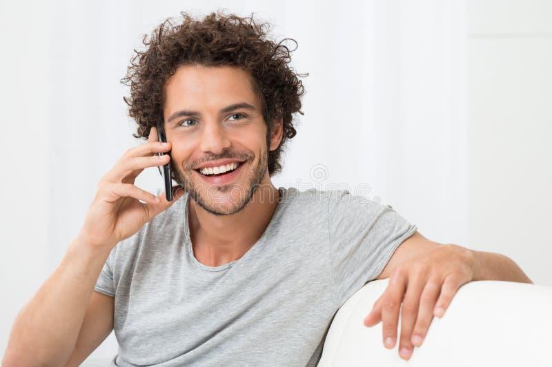 Jonge mens die op cellphone spreekt stock foto's