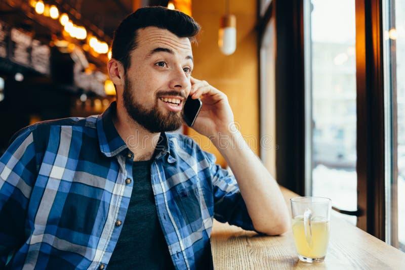 Jonge mens die op de telefoon in koffie spreken stock fotografie