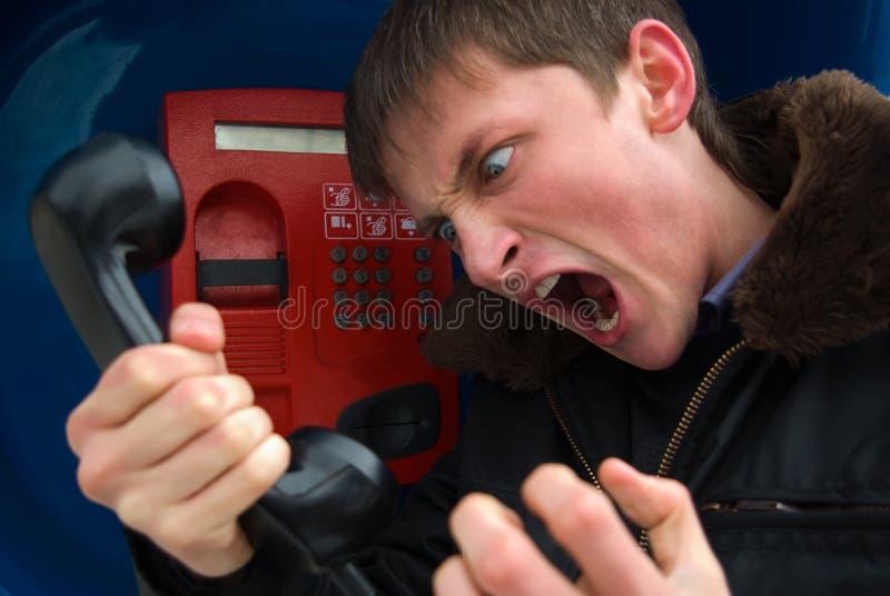 Jonge mens die op de telefoon met agressie spreekt stock foto's