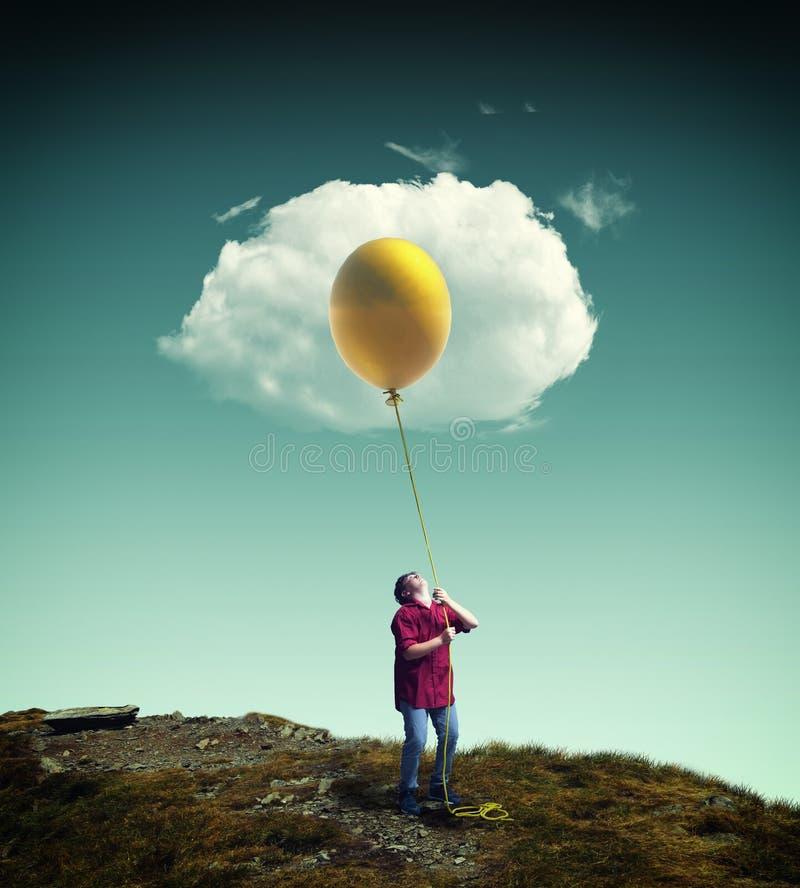 Jonge mens die op een gele ballon aan een wolk opheffen, stock fotografie